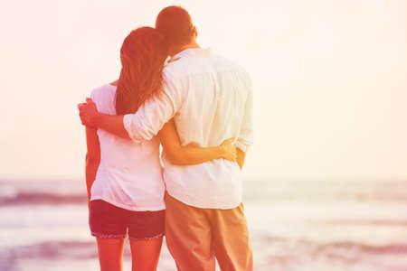 夕陽が美しいビーチを楽しんで幸せなロマンチックなカップル