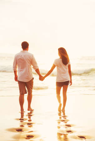 couple relaxing: Happy Romantic Couple Walking on the Beach Enjoying the Sunset