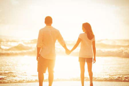 Feliz Caminar pareja romántica en la playa disfrutando de la puesta del sol Foto de archivo - 45968165