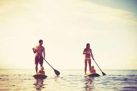 estilo de vida: Fam�lia que tem o divertimento Stand Up Paddling junto no oceano no nascer do sol