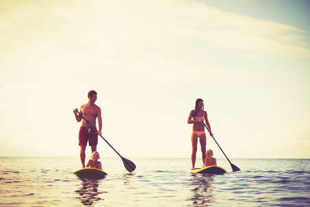 Family Having Fun Stand Up Paddling Together in the Ocean at Sunrise. Stock Photo
