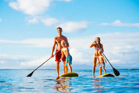 familias jovenes: Familia que se divierte Stand Up Remando juntos en el oc�ano en la hermosa ma�ana soleada