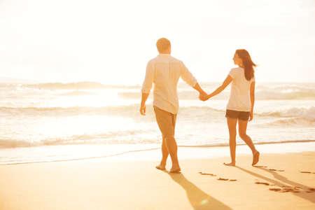 夕日を楽しんでビーチの上を歩く幸せなロマンチックなカップル