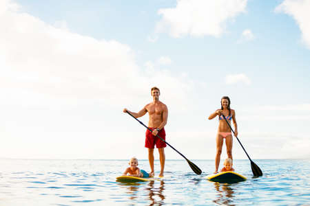 fun: Family Having Fun Stand Up Paddling Together in the Ocean on Beautiful Sunny Morning