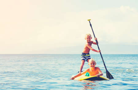 paddling: Young Boys Having Fun Stand Up Paddling Together in the Ocean