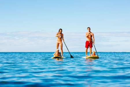 楽しい立ち上がる美しい晴れた朝に海に一緒にパドリングを持っている家族