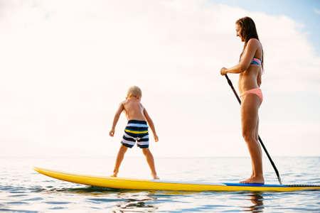 パドリングの海で楽しんで一緒に立ち上がる母と息子