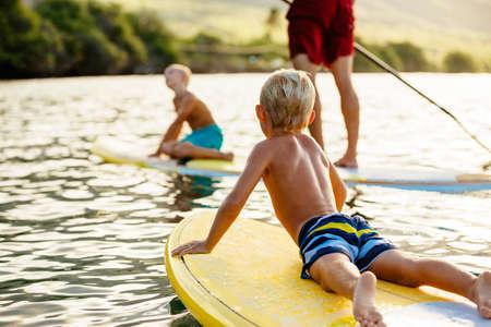 Famiglia che ha divertimento Stand Up Paddling insieme nell'oceano su Beautiful Sunny Morning Archivio Fotografico
