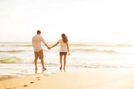 Glückliche romantische Paare zu Fuß am Strand genießen den Sonnenuntergang