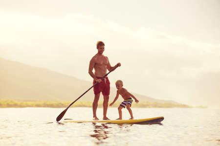viaje familia: Padre e Hijo Stand Up Remando en Sunrise Foto de archivo