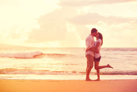 embraces: Happy Romantic Couple Kissing on the Beach at Sunset Stock Photo