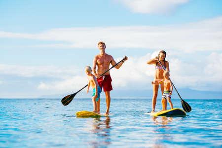楽しい立ち上がる美しい晴れた朝に海に一緒にパドリングを持っている家族 写真素材