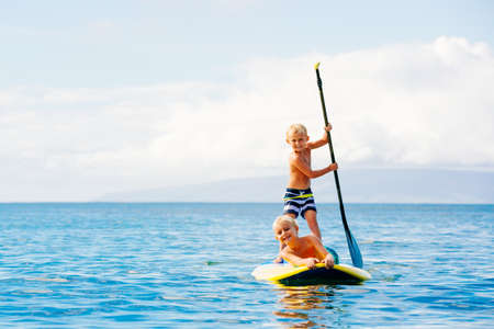 Young Boys Having Fun Stand Up Paddling Samen in de Oceaan Stockfoto