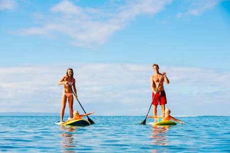 Familie, die Spaß Stand Up Paddling zusammen im Ozean auf schöner sonniger Morgen Standard-Bild