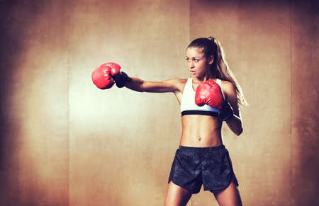 fitness model: Beautiful Woman with the Red Boxing Gloves. Attractive Female Boxer Training. Stock Photo
