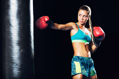 Beautiful Woman with the Red Boxing Gloves. Attractive Female Boxer Training. Фото со стока