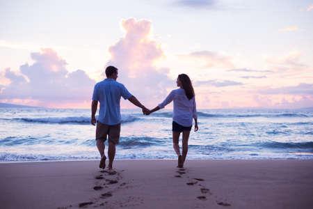 열대 휴가에 일몰 해변에 산책하는 젊은 연인