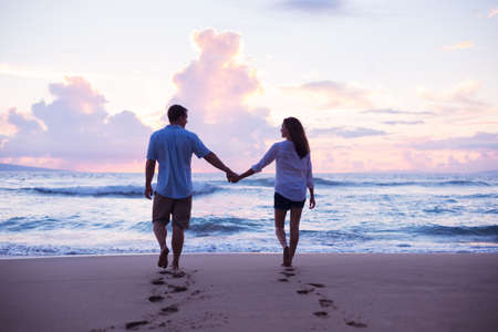 lovers embracing: Young Lovers Walking on the Beach at Sunset on Tropical Vacation