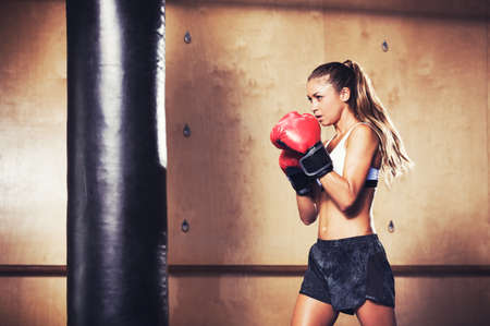 boxing sport: Beautiful Woman with the Red Boxing Gloves. Attractive Female Boxer Training. Stock Photo