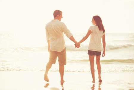 Feliz pareja joven romántica caminando por la playa al atardecer en vacaciones