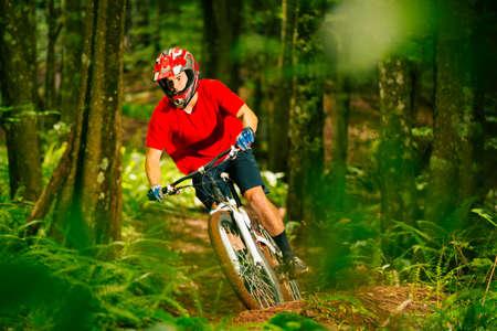 mountain biker: Mountain Biker Riding Down Beautiful Lush Forest Trail in the Mountains