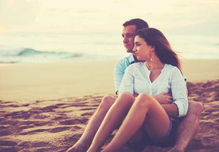 luna de miel: Feliz joven pareja romántica de relax en la playa viendo la puesta del sol. Vacaciones Escapada de luna de miel.
