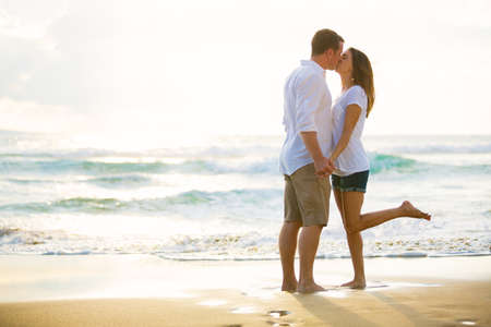 Romantic Happy Young Couple Kissing on the Beach at Sunset