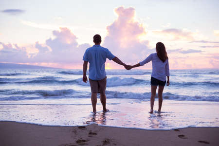 two hands: Young Lovers Walking on the Beach at Sunset on Tropical Vacation
