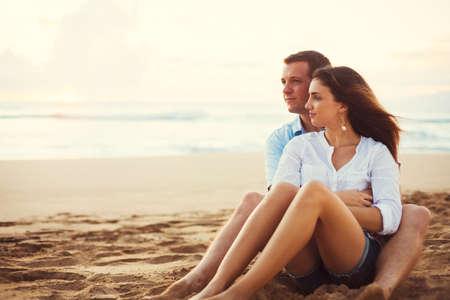 ロマンス: 幸せな若いロマンチックなカップル、サンセットを見ながらビーチでリラックス。新婚旅行のバケーション。
