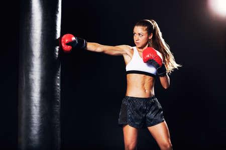 Mooie Fitness Vrouw met de Rode bokshandschoenen. Aantrekkelijke Vrouwelijke Boxer Training ponsen een zware tas in de sportschool.