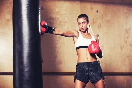 boxeador: Hermosa mujer de la aptitud con los guantes de boxeo rojos. Atractiva Mujer boxeador Entrenamiento perfora un bolso pesado en el gimnasio.