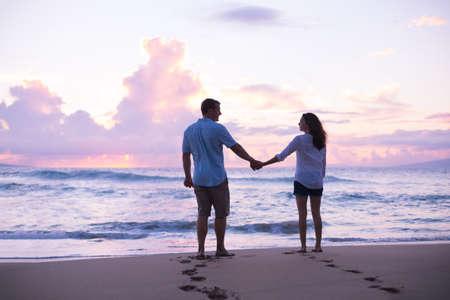 Jonge geliefden lopen op het strand bij zonsondergang op tropische vakantie