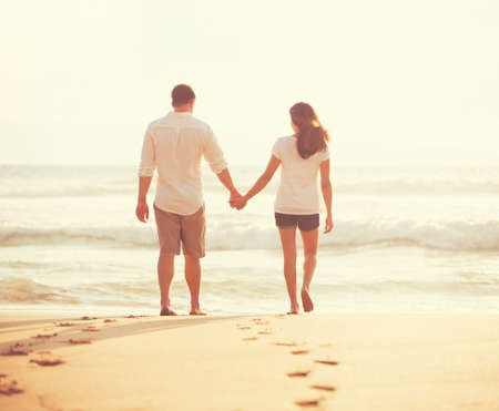 human relationship: Romantic Young Lovers Walking Down the Beach at Sunset on Vacation