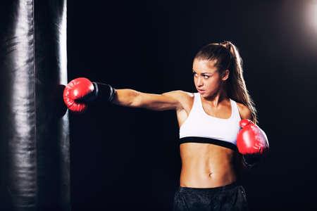 赤いボクシング グローブと美しいフィットネス女性。魅力的な女性ボクサーのトレーニング ジムで重いバッグをパンチします。