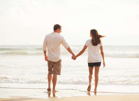 Pares novos românticos felizes que andam abaixo da praia no por do sol em férias