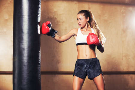 kickboxing: Beautiful Fitness Woman with the Red Boxing Gloves. Attractive Female Boxer Training Punching a Heavy Bag in the Gym.