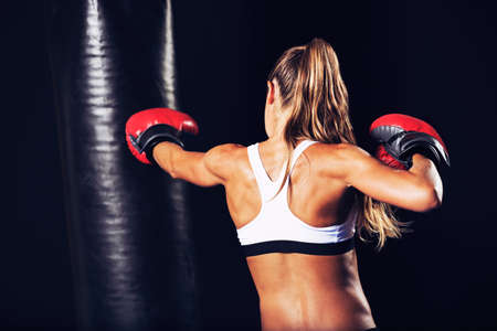 Beautiful Woman with the Red Boxing Gloves. Attractive Female Boxer Training. 스톡 콘텐츠