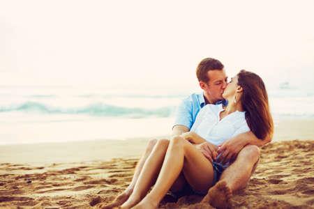 pareja abrazada: Feliz joven pareja romántica de relax en la playa. Besar y ver el atardecer