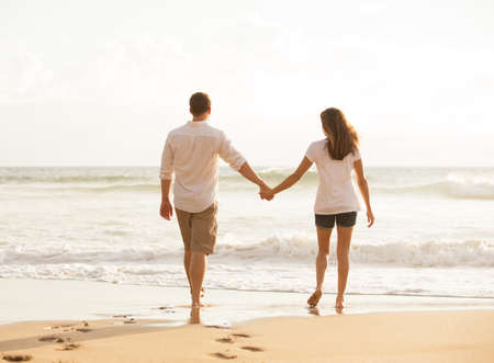 femme romantique: Romantic Young Lovers Walking Down the Beach at Sunset on Vacation