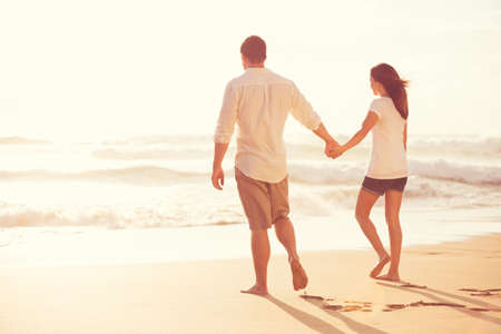 Happy Romantic Young Couple Walking Down the Beach at Sunset on Vacation