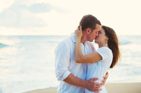 Romantische gelukkige jonge paar kussen op het strand bij zonsondergang