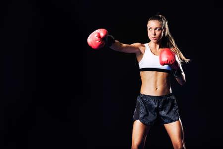 赤いボクシング グローブと美しい女性。魅力的な女性ボクサーのトレーニング。