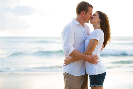parejas: Romantic Happy Young Couple Kissing on the Beach at Sunset