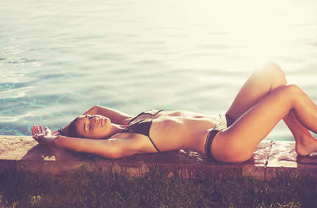 relax: Fashion lifestyle, beautiful woman in swimwear relaxing by the pool at sunset