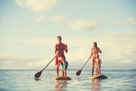 Family stand up paddling at sunrise, Summer fun outdoor lifestyle Stock Photo