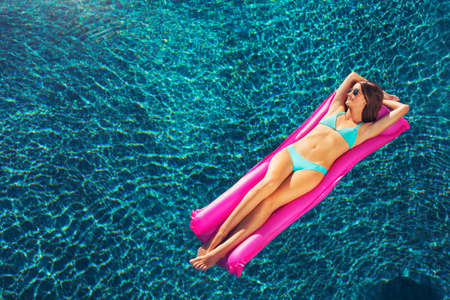 Beautiful sexy woman relaxing floating on raft in luxury swimming pool