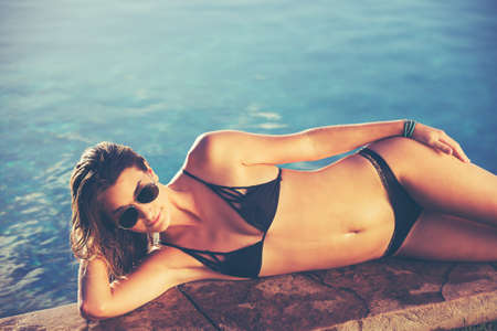 women legs: Fashion lifestyle, beautiful woman in swimwear relaxing by the pool at sunset