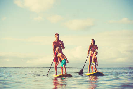 Family stand up paddling at sunrise, Summer fun outdoor lifestyle Standard-Bild