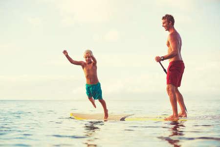 Vader en zoon staan ??peddelen bij zonsopgang, pret van de zomer outdoor lifestyle Stockfoto - 47342883