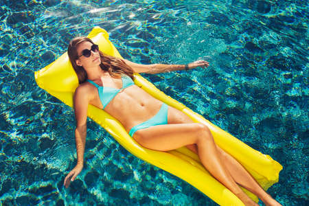 float: Beautiful sexy young woman in bikini relaxing floating on raft in luxury swimming pool
